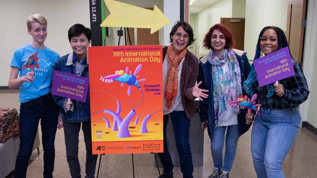 Experimental Animation lab team posing next to a poster for Animation Day 2019